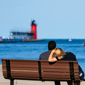 Man and woman sitting on a bench overlookign the harbor and the South Haven lighthouse